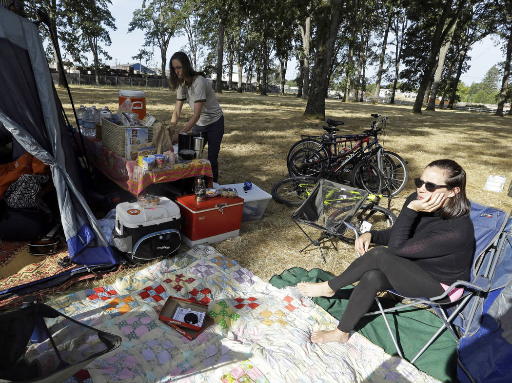 Hilary O'Hollaren, right, sits in the early morning sun as Rory O'Hollaren prepares breakfast as they camp near the state fairgrounds in preparation for the Aug. 21, 2017, solar eclipse in Salem,  ...
