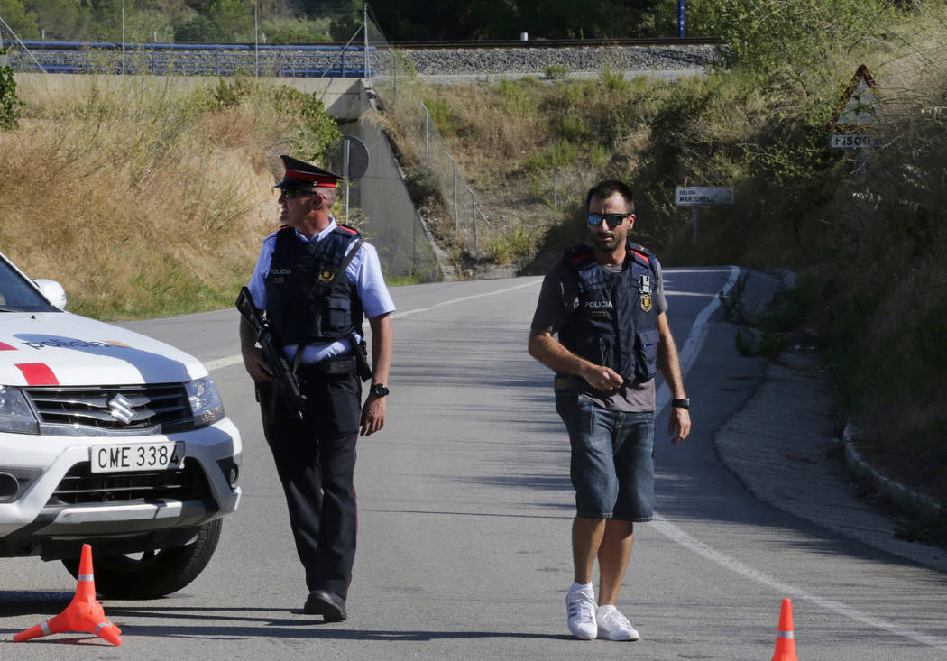 Armed police officers stand guard near Subirats, Spain, Monday, Aug. 21, 2017. A police operation was underway Monday in an area west of Barcelona, and a Spanish newspaper reports that the fugitiv ...