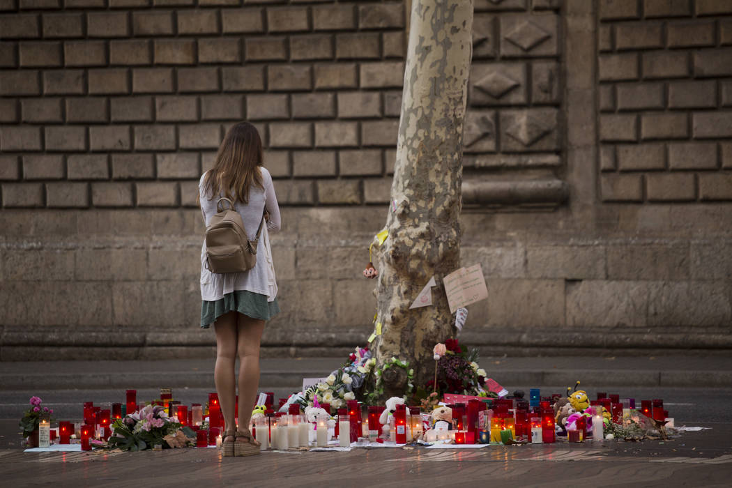 A woman stands next to candles and flowers after a van attack that killed at least 14 people in Las Ramblas promenade, Spain, Monday, Aug. 21, 2017. (AP Photo/Emilio Morenatti)