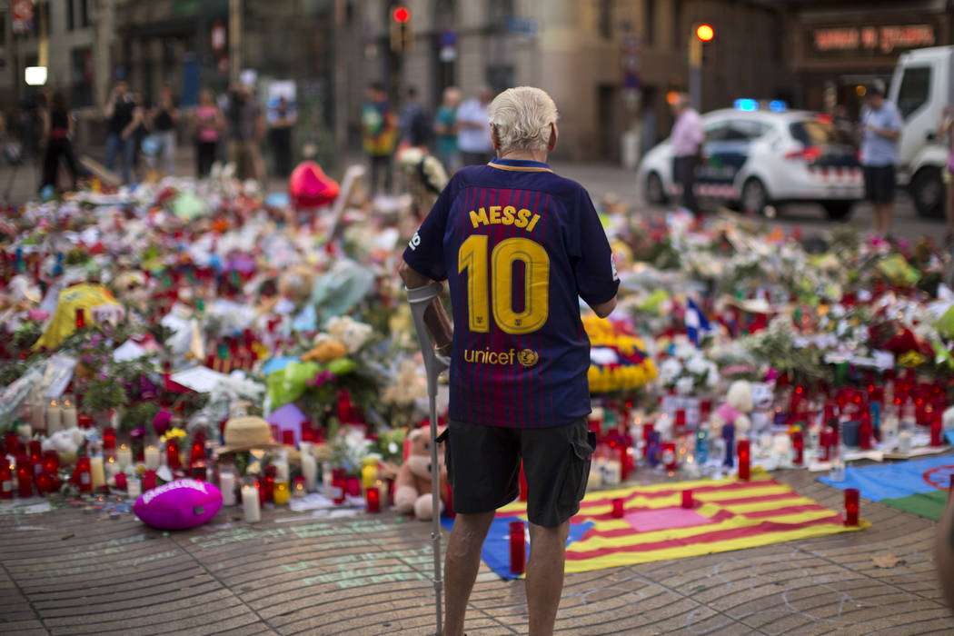 A man stands next to flags, flowers, messages and candles to the victims on Barcelona's historic Las Ramblas promenade on the Joan Miro mosaic, embedded in the pavement where the van stopped after ...