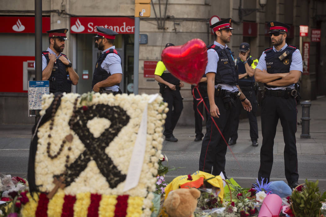 Police officers stand guard next to flags, flowers, messages and candles to the victims on Barcelona's historic Las Ramblas promenade on the Joan Miro mosaic, embedded in the pavement where the va ...