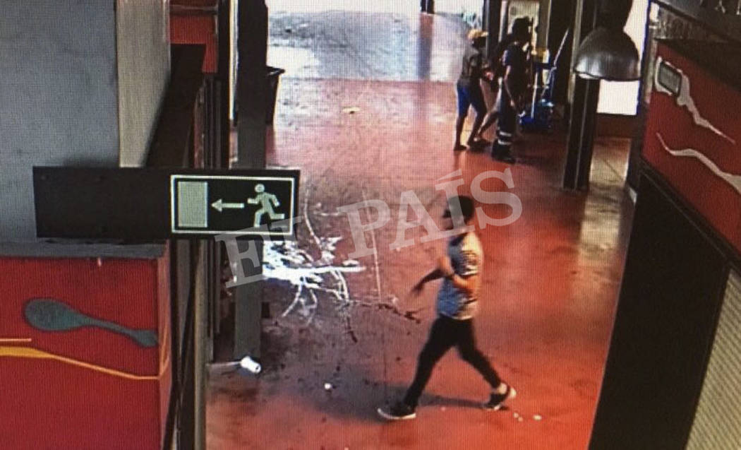 In this watermarked frame grab from CCTV released by the Spanish newspaper El Pais on Monday Aug. 21, 2017, a suspect. believed to be Younes Abouyaaqoub is is captured by a security camera walking ...
