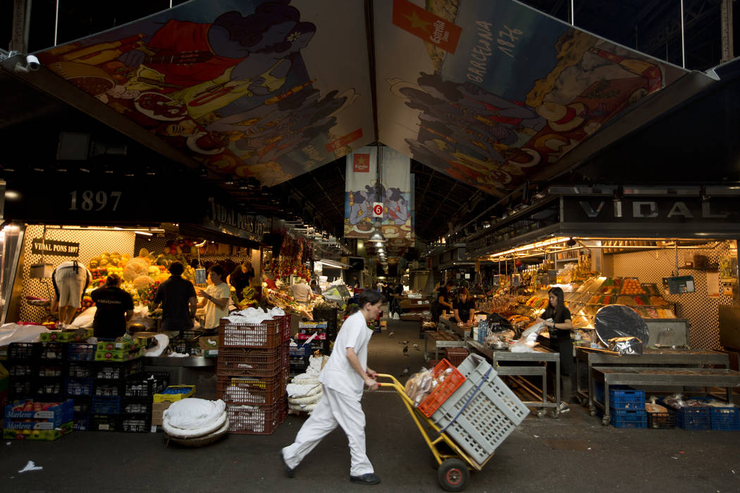 Vendors prepare their stalls at the Boqueria market in Raval, the neighbourhood in central Barcelona where the vehicle attack took place, in Barcelona, Spain, Spain, Monday, Aug. 21, 2017. (AP Pho ...