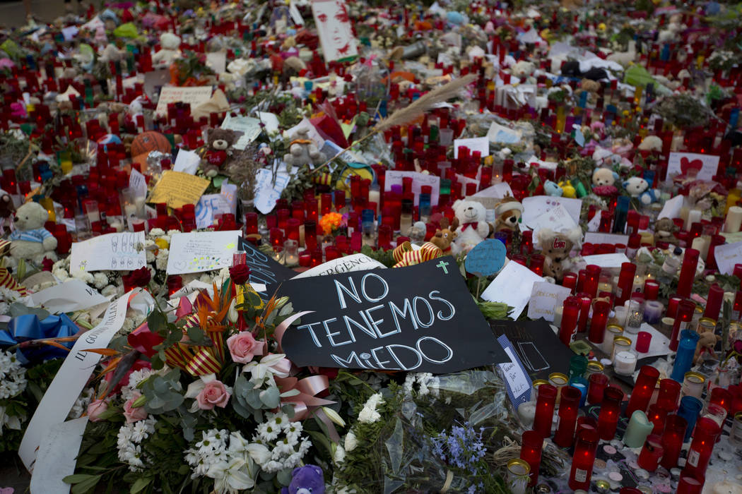 "A banner reading in Spanish ""We are not afraid"" is seen next to flags, flowers, messages and candles to the victims on Barcelona's historic Las Ramblas promenade on the Joan Miro ..."