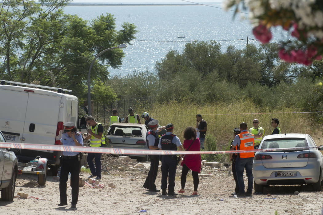 In this photo taken on Thursday, Aug. 17, 2017, emergency team members collect evidence at the explosion site where the attacks of Barcelona were planned, in Alcanar, Tarragona province, Spain. A  ...