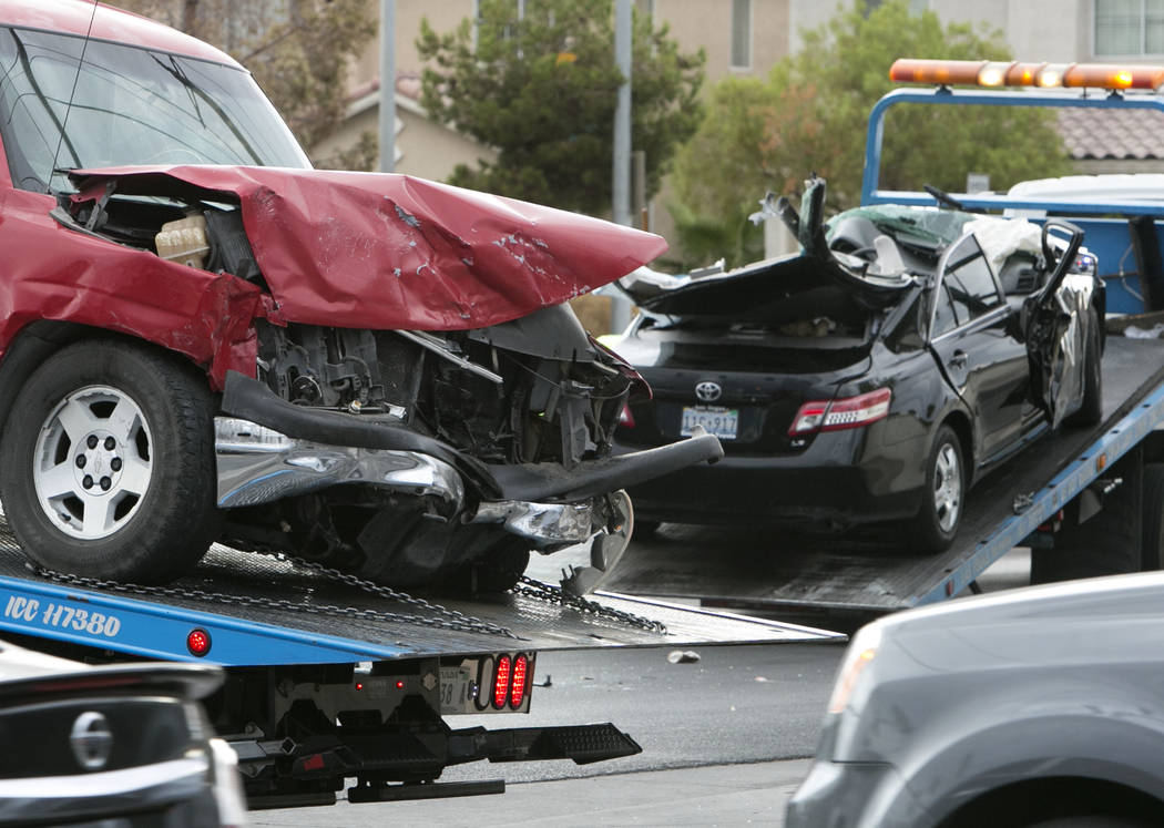 Cars involved in an accident get towed away on Monday, Aug. 21, 2017, in Las Vegas. A Chevrolet SUV ran a red light at the intersection of Stewart Avenue and North Christy Lane and crashed into a  ...