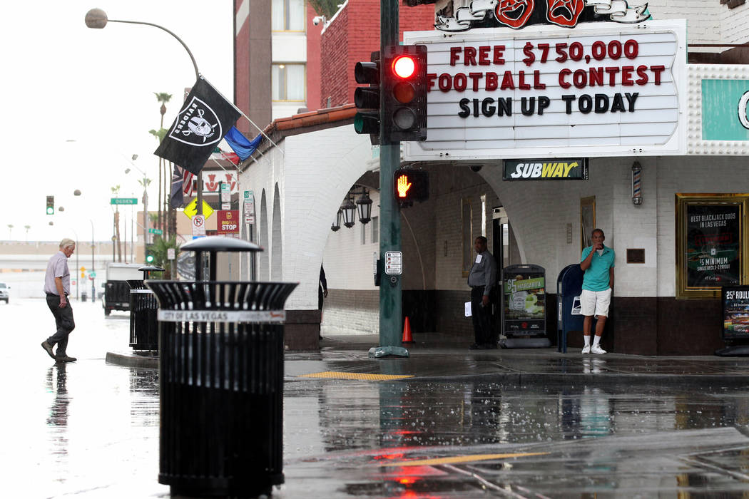 People brave a light rain on East Fremont Street at North 6th Street in downtown Las Vegas on Monday, Aug. 21, 2017. (K.M. Cannon/Las Vegas Review-Journal) @KMCannonPhoto
