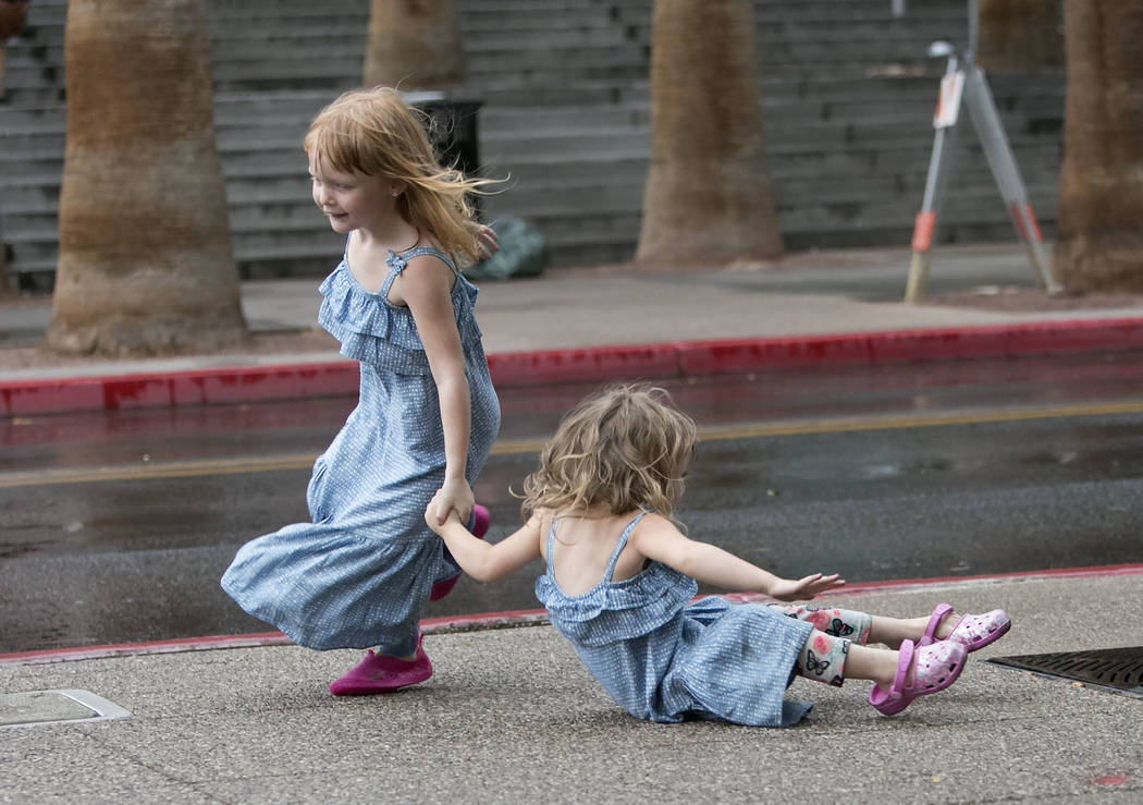 Brooke Collier, 3, is helped by her sister Luxee, 5, after she fall as they run for shelter during the rain fall on Monday, Aug. 21, 2017, in Las Vegas. (Bizuayehu Tesfaye/Las Vegas Review-Journal ...