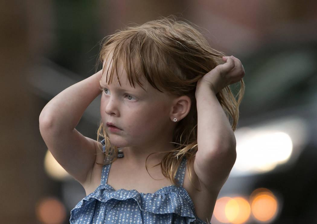 Luxee Collier, 5, fixes her wet hair as light rain falls on Monday, Aug. 21, 2017, in Las Vegas. (Bizuayehu Tesfaye/Las Vegas Review-Journal) @bizutesfaye