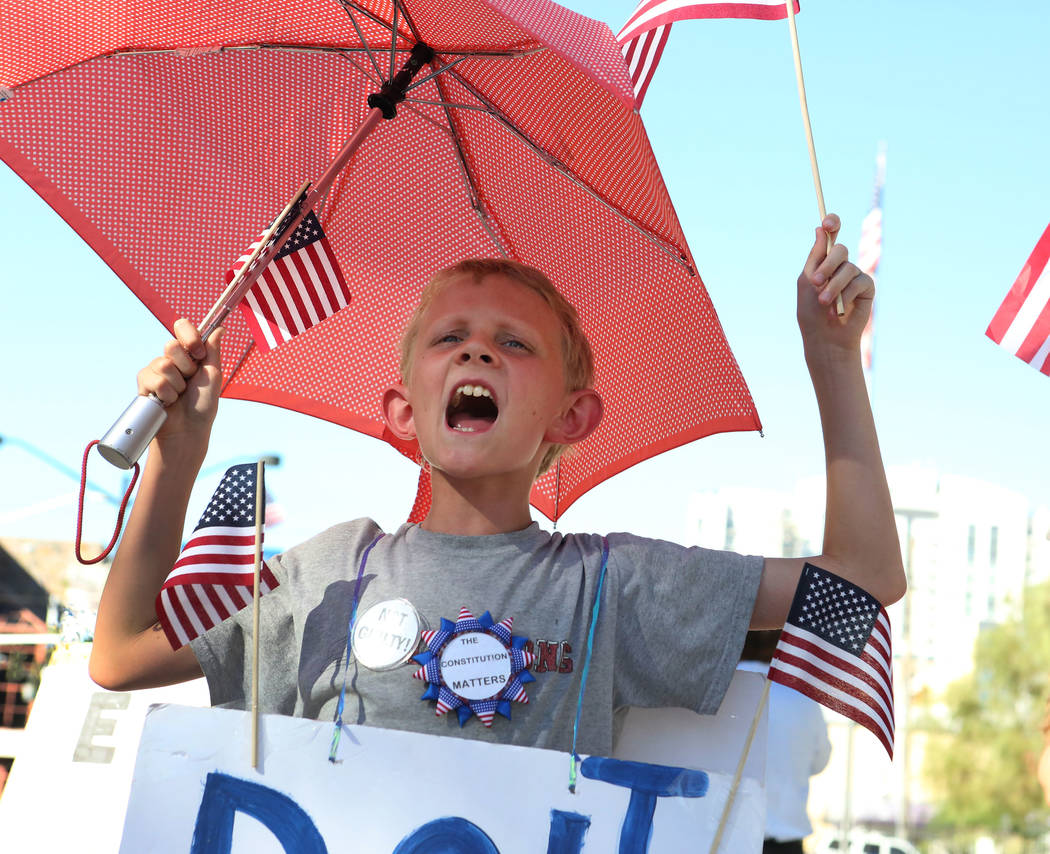 "Austin Shelby of North Las Vegas celebrates outside the Lloyd George U.S. Courthouse on Las Vegas Boulevard waving flags and wearing a sign that reads ""D.O.J. Lies"" after the not guilty verdic ..."