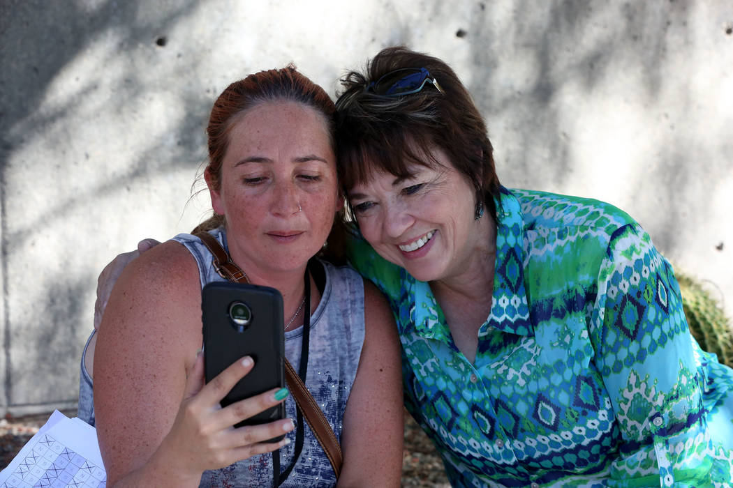 Carol Bundy, right, hugs Andrea Parker, wife of Eric Parker, outside the Lloyd George U.S. Courthouse as she does a live broadcast that her husband and other defendants were found not guilty in th ...
