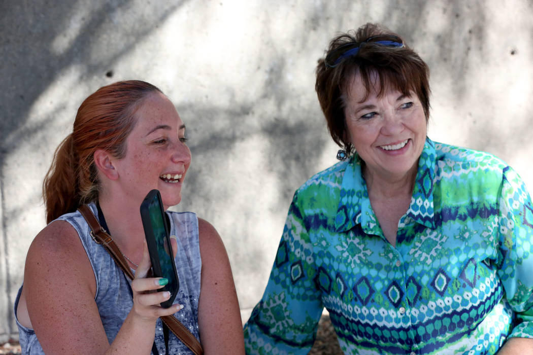 Sitting next to Carol Bundy, Andrea Parker, left, wife of Eric Parker turns her phone to the scene outside the Lloyd George U.S. in Las Vegas during a live broadcast to announce that her husband a ...