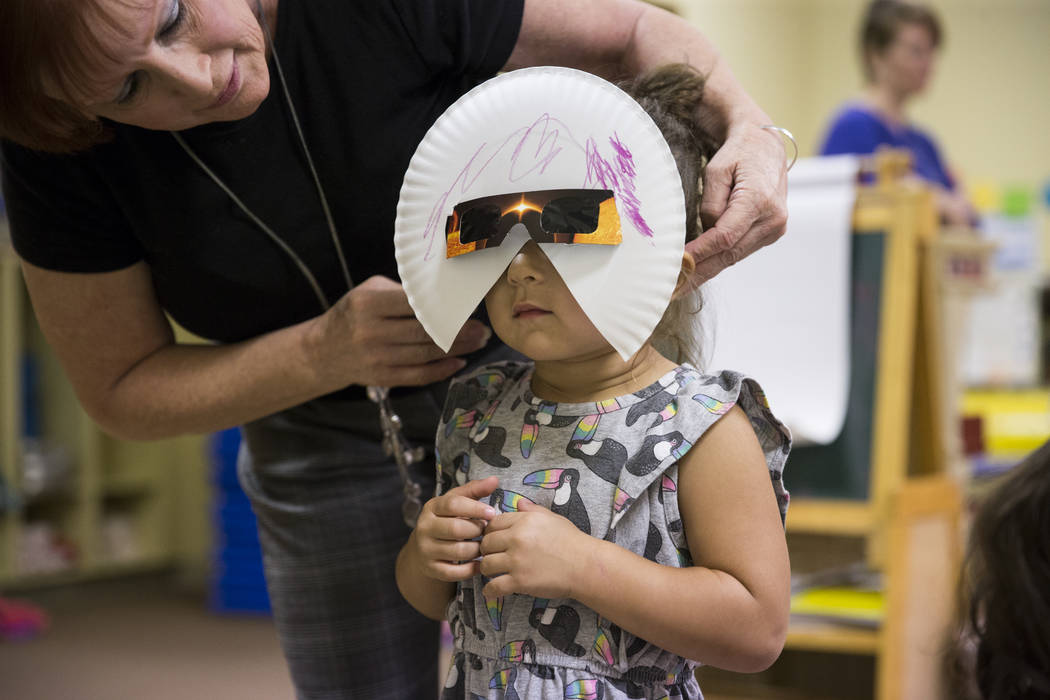 Amy Robinson, director of Keeping Youth Educated daycare, helps Sofia Hernandez-Bernabei, 3, fit her solar eclipse glasses before stepping outdoors in Las Vegas, on Monday, Aug. 21, 2017. Erik Ver ...