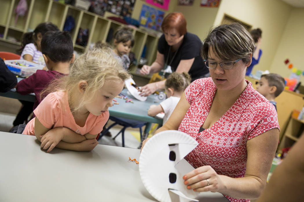 Emma Pease-Byron, right, helps her daughter's friend Amilya Durnen, 3, with her solar eclipse glasses before going outside to watch eclipse at the Keeping Youth Educated daycare in Las Vegas, on M ...