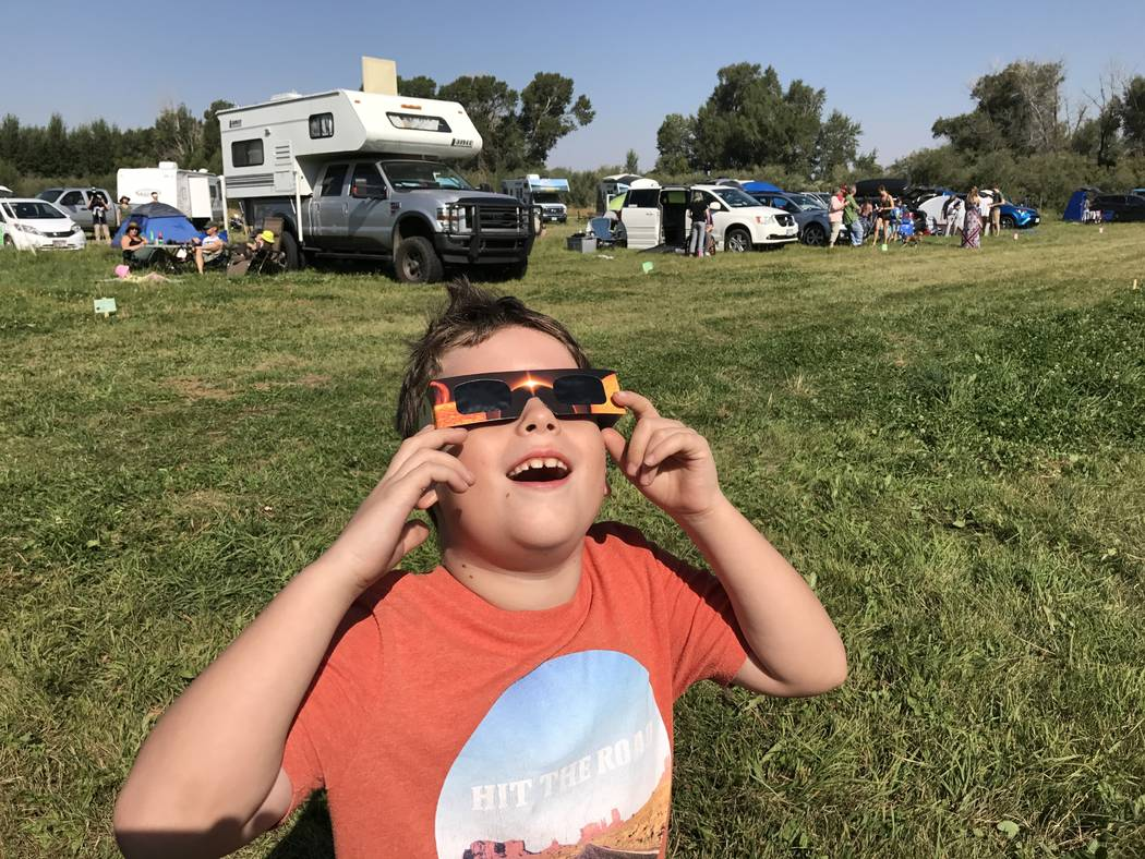 George Brean, 7, of Las Vegas watches from a field in Rigby, Idaho, as the moon begins to move across the sun Monday. Henry Brean/Las Vegas Review-Journal