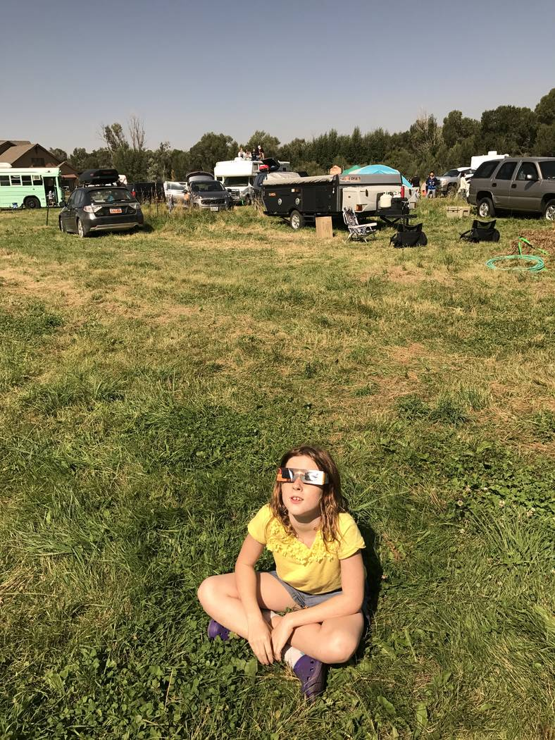 Lilah Brean, 10, of Las Vegas, watches the early stages of Monday's eclipse from a field in Rigby, Idaho. Henry Brean/Las Vegas Review-Journal