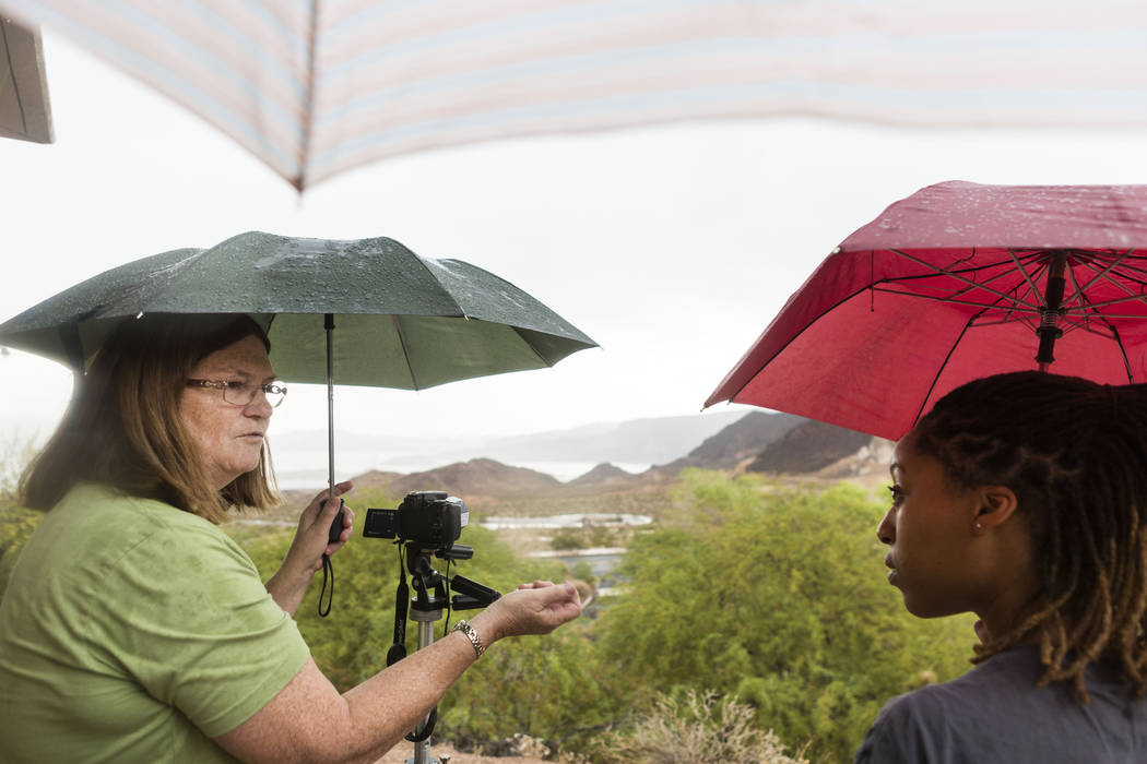 Charlene Wiesenborn, left, and DeShaunna Gee wait for the dominating clouds to part so they can witness the partial solar eclipse during the during the eclipse viewing party at the Lake Mead Visit ...