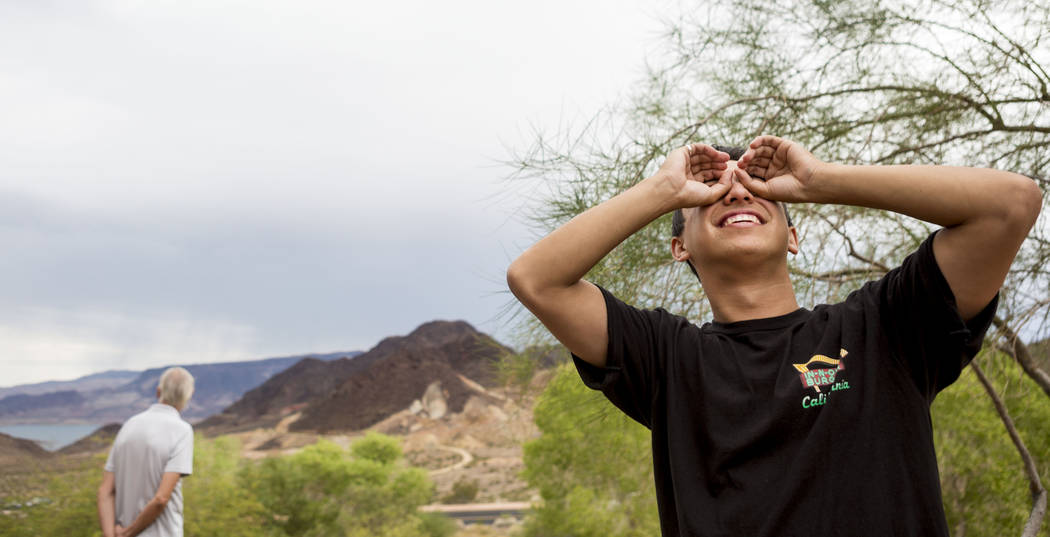 Juan Ruiz attempts to use his hands to see through the dense and witness the solar eclipse during the eclipse viewing party at the Lake Mead Visitor Center in Boulder City, Monday, Aug. 21, 2017.  ...
