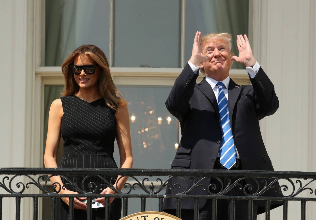 President Donald Trump, accompanied by first lady Melania Trump, gestures at the White House in Washington, Monday, Aug. 21, 2017, as they viewed the solar eclipse. (AP Photo/Andrew Harnik)