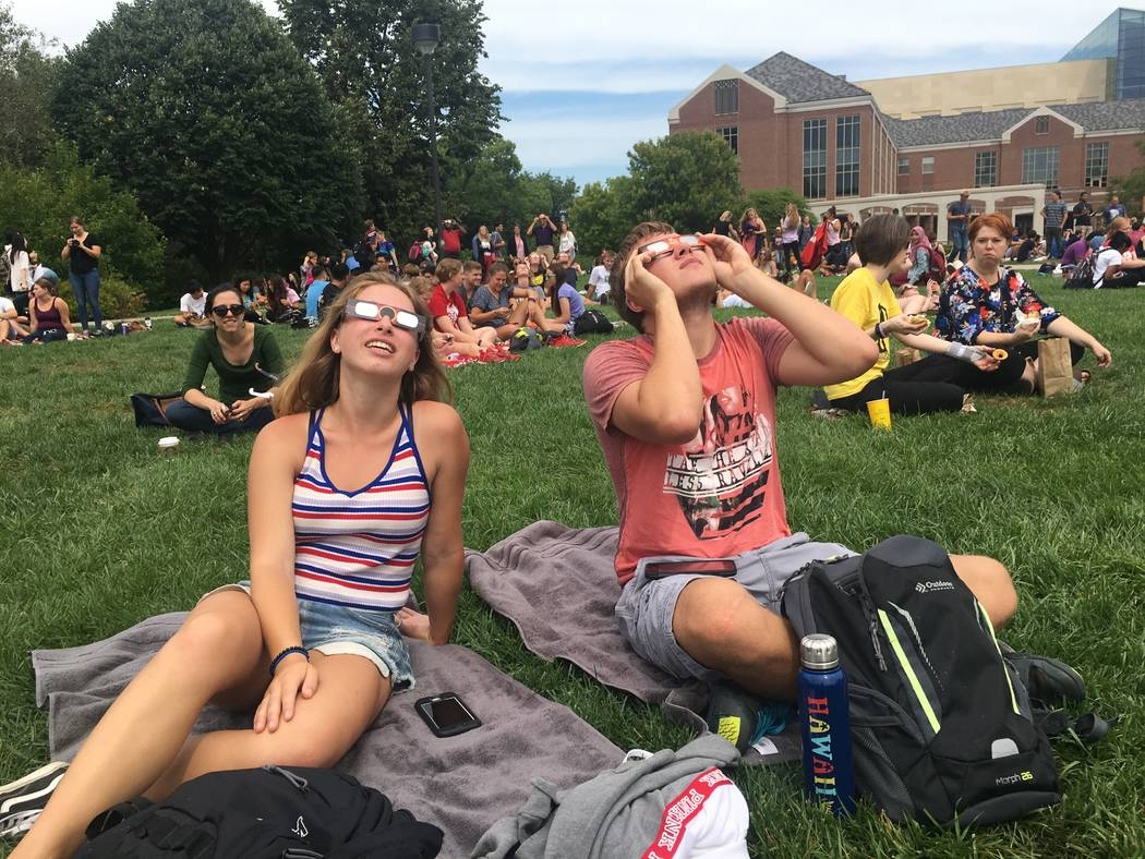 University of Nebraska-Lincoln students Maya McIntosh and Garrett Brockman gaze up toward the sun during Monday's eclipse. (Bailey Schulz/Las Vegas Review-Journal)