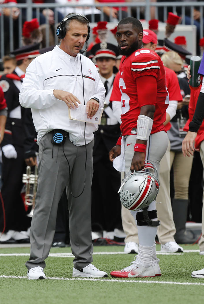 FILE - In this Oct. 1, 2016, file photo, Ohio State coach Urban Meyer, left, and quarterback J.T. Barrett talk during a timeout against Rutgers in the first half of an NCAA college football game i ...