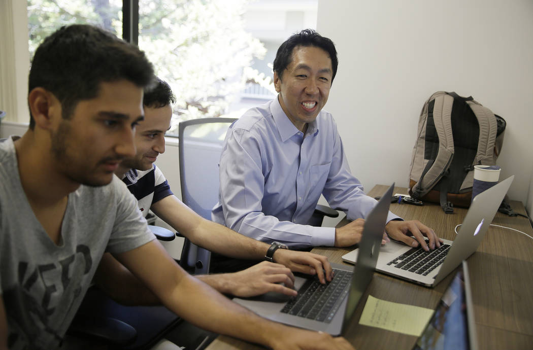 In this Friday, July 14, 2017, photo, computer scientist Andrew Ng, right, works with others at his office in Palo Alto, Calif. Ng, one of the world's most renowned researchers in machine learning ...