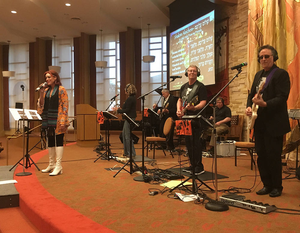 Cantor Jessica Hutchings, left, sings along to music performed by Shabbatones members Brad Torchin, from right, Mike Adler, Ira Spector, David Miller, Eddie Birch and Glori Rosenberger. (Brian San ...