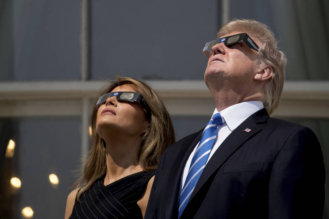 President Donald Trump and first lady Melania Trump wear protective glasses as they view the solar eclipse, Monday, Aug. 21, 2017, at the White House in Washington. (AP Photo/Andrew Harnik)