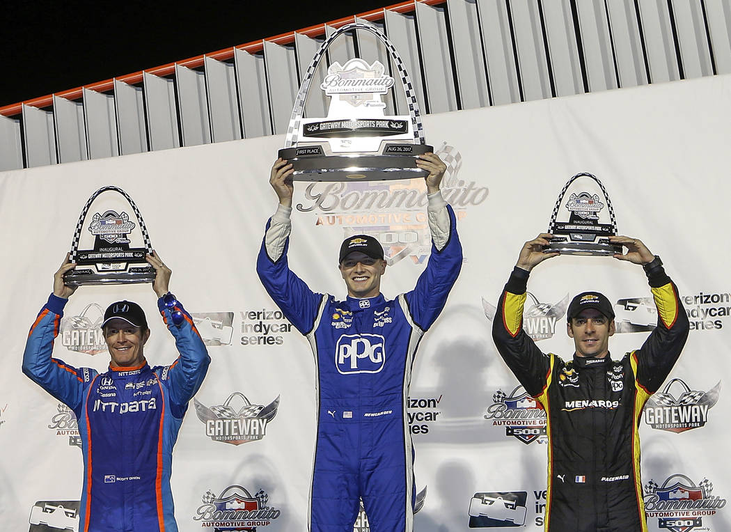 Josef Newgarden, center, celebrates his win, while standing next to second-place Scott Dixon, left, of New Zealand, and third-place Simon Pagenaud, of France, after the IndyCar auto race Saturday, ...