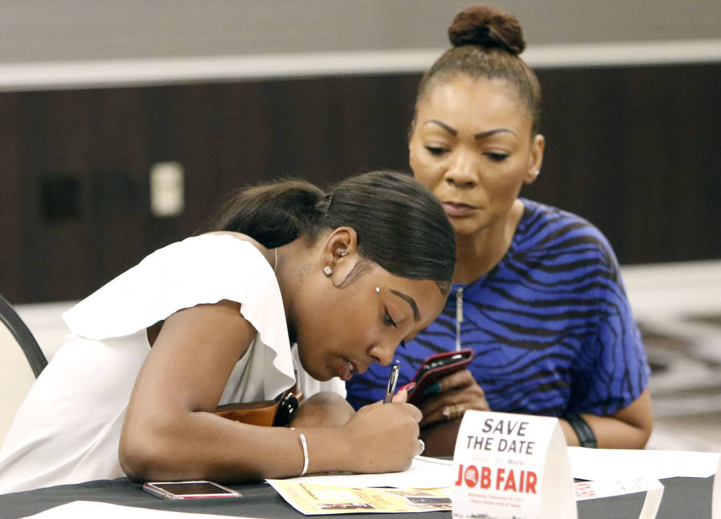 Candice McFarland, left, fills out her job application form as her mother Stephanie looks on during a job fair hosted by the Las Vegas Review-Journal at Palace Station on Thursday, Aug. 17, 2017,  ...