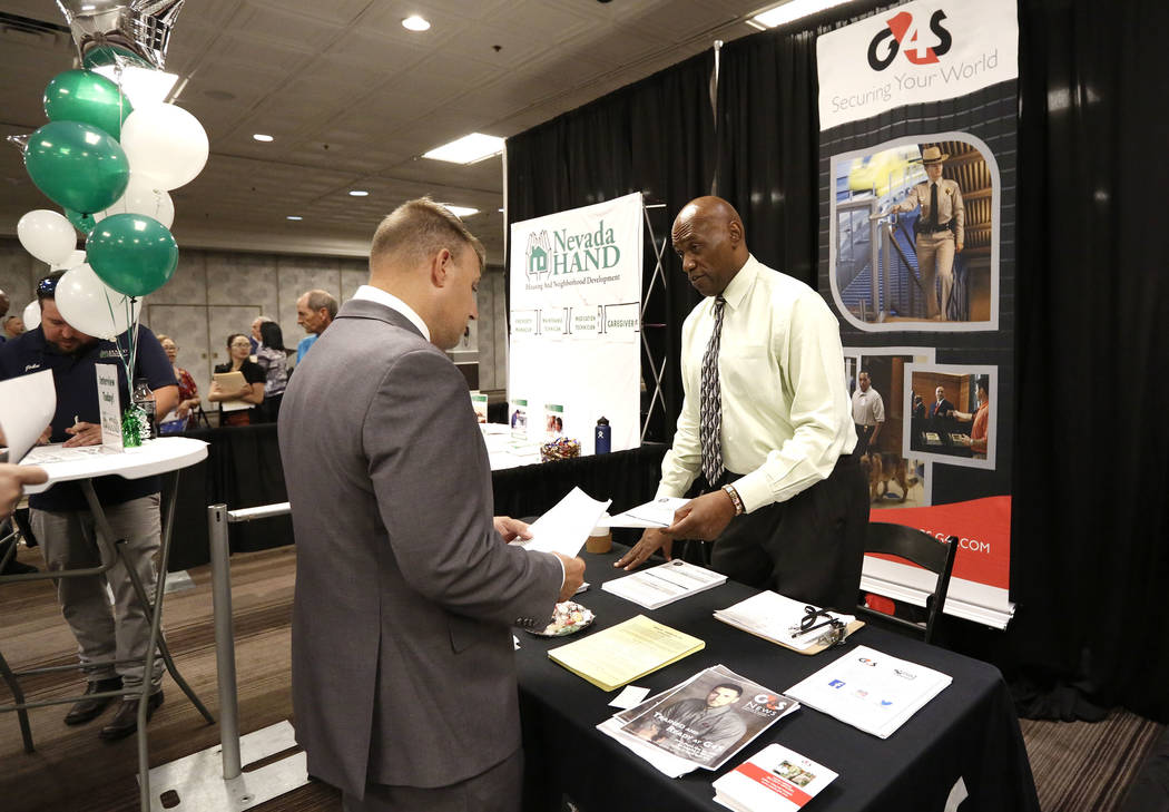 Human Resources Manager at G4S Secure Solutions, Inc., Timothy Wells, right, talks to a job seeker during a job fair hosted by the Las Vegas Review-Journal at Palace Station on Thursday, Aug. 17,  ...