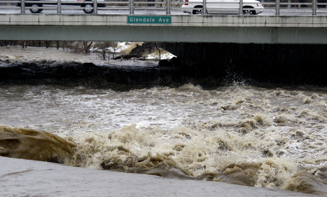 Traffic crosses the raging Truckee River, Sunday, Jan. 8, 2017, where it runs near the Grand Sierra hotel-casino along a line that divides the cities of Reno and Sparks, Nev. (AP Photo/Scott Sonner)
