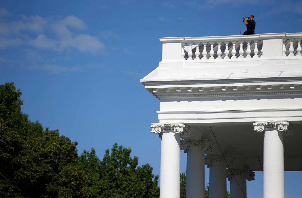A Secret Service officer looks out from the roof of the North Portico in reaction to an apparent fence jumper at the White House in Washington, D.C., May 16, 2017. (Joshua Roberts/Reuters)