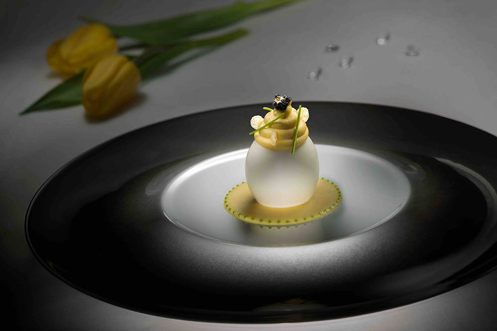 L'Atelier de Joël Robuchon's summer menu includes L'oeuf de poule, a semi-soft boiled egg on a spinish puree with comte, cheese sauce. (Courtesy)
