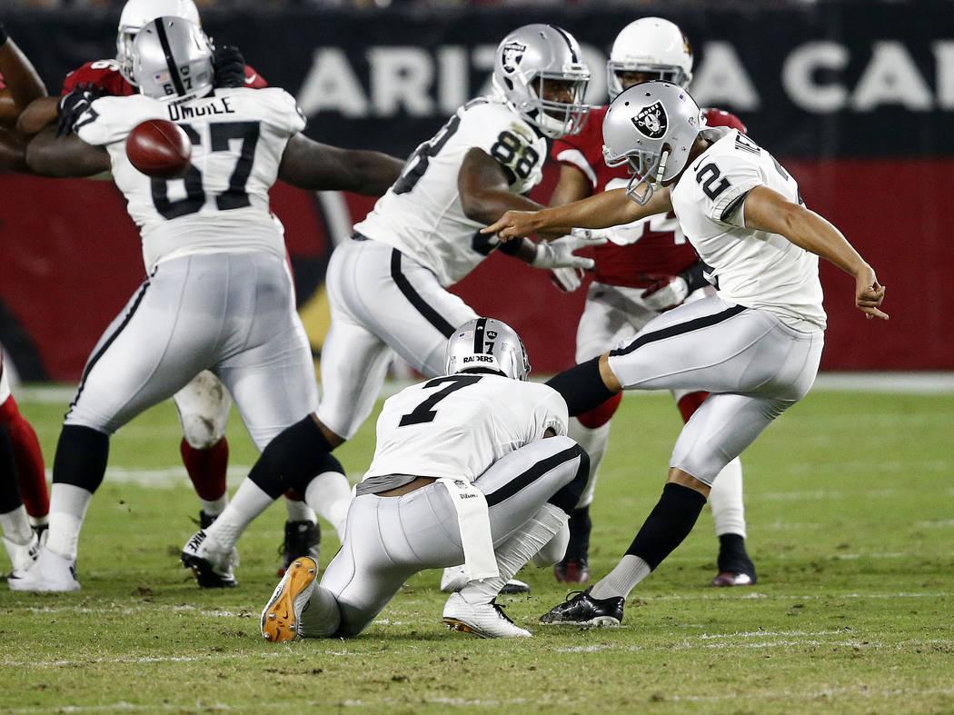 Oakland Raiders' Giorgio Tavecchio (2) kicks a field goal as Marquette King (7) holds during the first half of an NFL preseason football game agains the Arizona Cardinals, Saturday, Aug. 12, 2017, ...