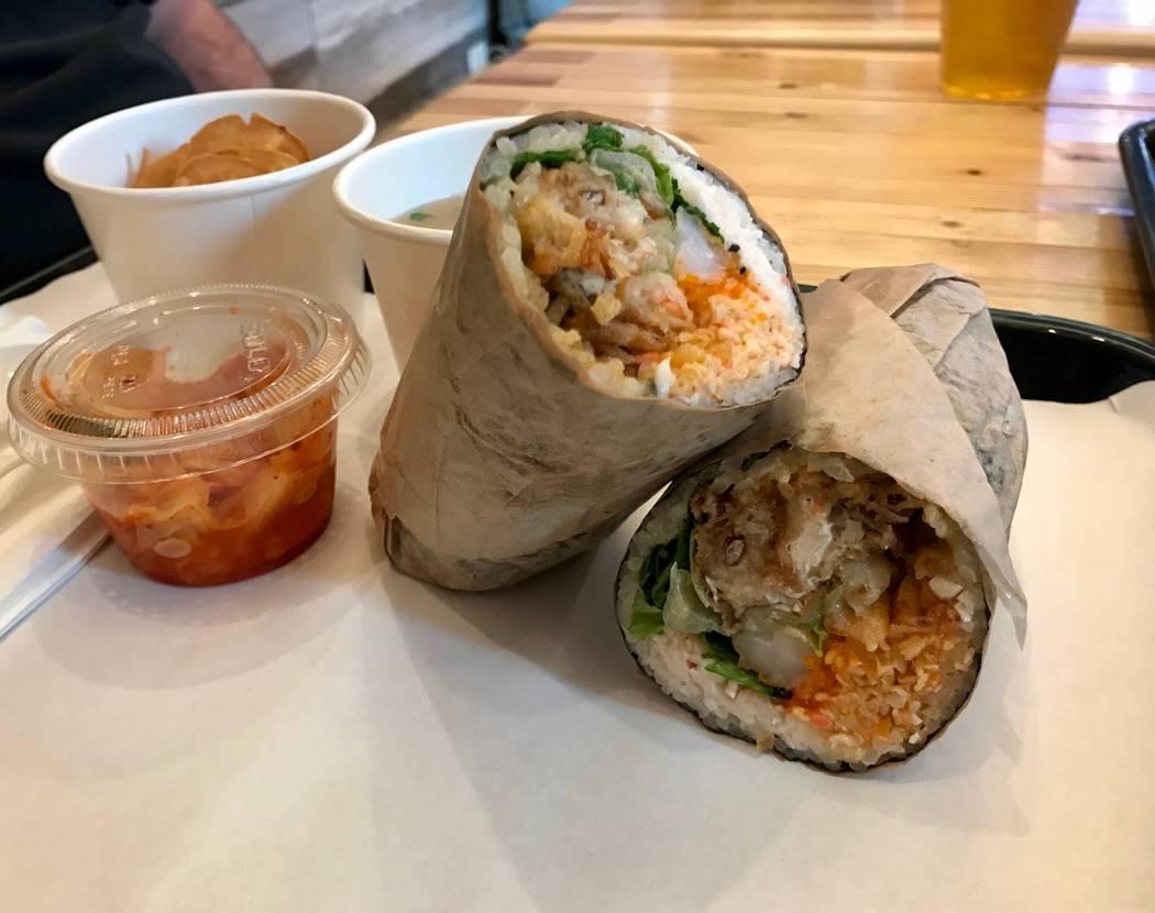"The ""Blue Ocean"" sushi burrito is pictured ($10.95), which includes soft-shell crab, spicy crab mix, masago (smelt roe), shrimp tempura, onion tempura, cilantro, lettuce, furikake, sesame and eel  ..."