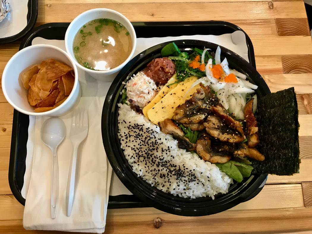 An eel unagi bowl ($11.95) is pictured with eel, crab mix, spicy tuna, tamago (egg), masago (smelt roe), seaweed salad, seaweed paper and sushi rice on a bed of mixed greens. Dine-in customers rec ...