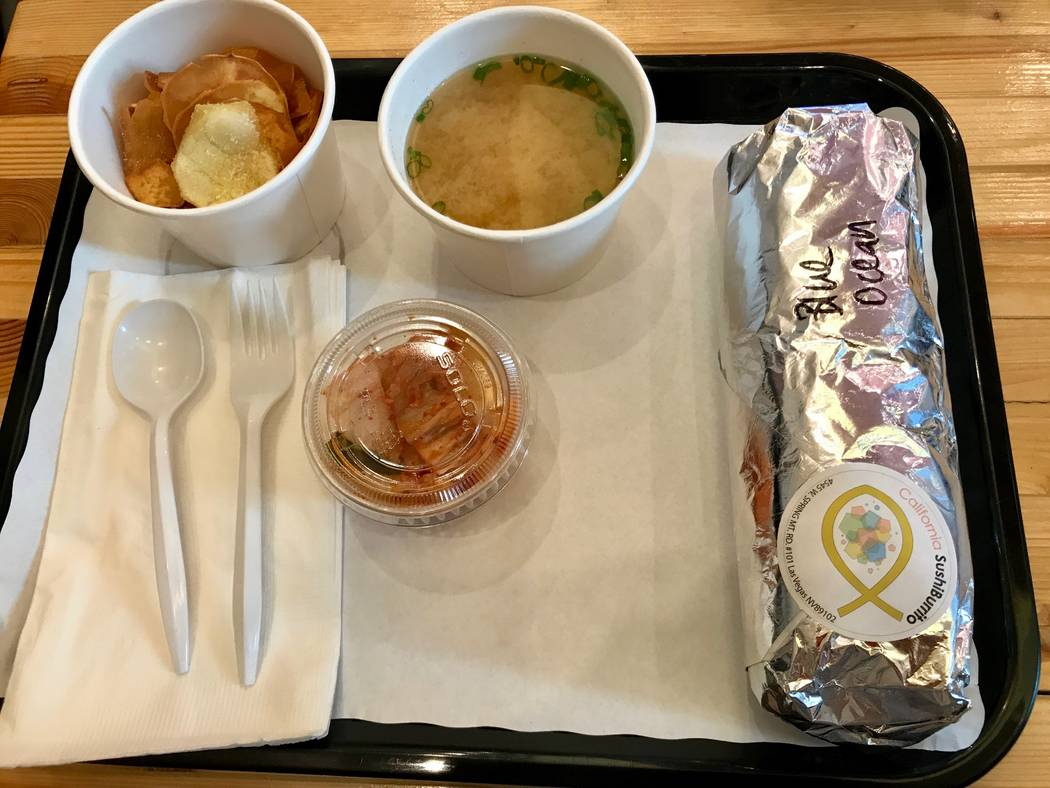 """The """"Blue Ocean"""" sushi burrito ($10.95) presented before unwrapping. Dine-in customers receive complimentary miso soup and every bowl and burrito comes with a side of sweet potato chips. (Madelyn  ..."""