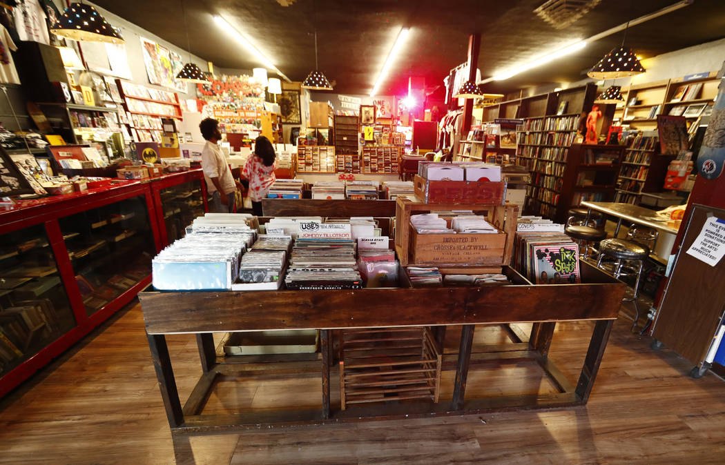 In this Sunday, Aug. 20, 2017, photo, customers pick through the records on display inside of an information cafe called Mutiny in south Denver. Shop owner Jim Norris is hoping to license his stor ...