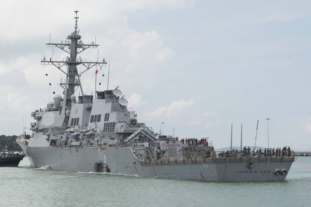 In this Aug. 21, 2017, photo provided by U.S. Navy, the guided-missile destroyer USS John S. McCain (DDG 56) steers towards Changi Naval Base, Singapore, following a collision with the merchant ve ...