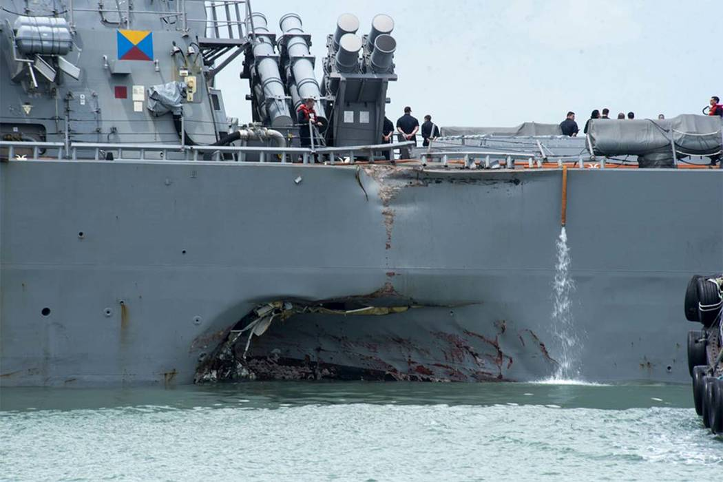 Damage to the portside is visible as the Guided-missile destroyer USS John S. McCain (DDG 56) steers towards Changi naval base in Singapore following a collision with the merchant vessel Alnic MC  ...
