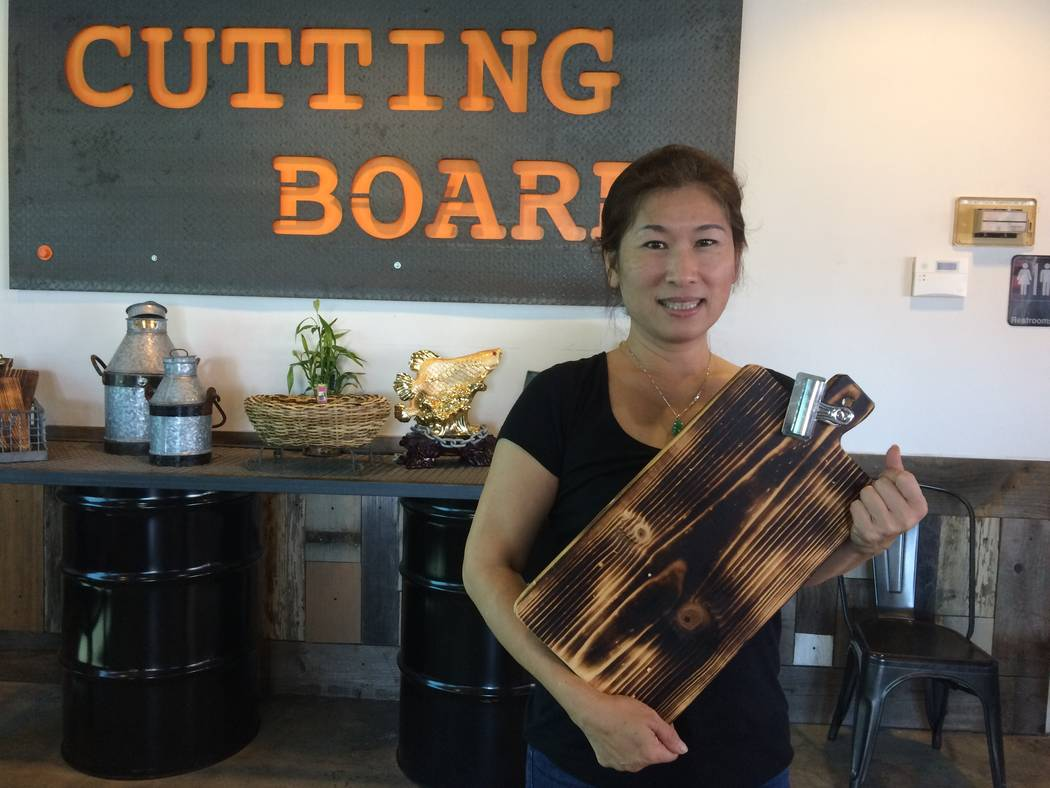 Tiffany Le holds a cutting board Aug. 21, 2017, at Cutting Board Filipino Gastropub, 2131 Rock Springs Drive. She is one of the partners and can make suggestions should one not be familiar with Fi ...