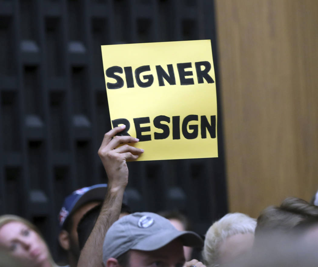 A sign asks Mayor Mike Signor to resign during the Charlottesville City Council meeting Monday, Aug. 21, 2017, in Charlottesville, Va. Anger boiled over at the first Charlottesville City Council m ...