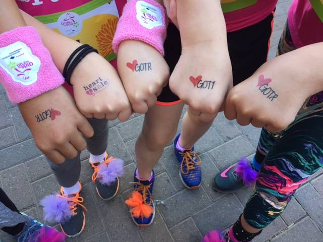 Stamps hands are seen before the 2016 Girls On the Run 5K event. The program includes physical exercise but also helps develop character and a sense of belonging. (Girls On the Run)