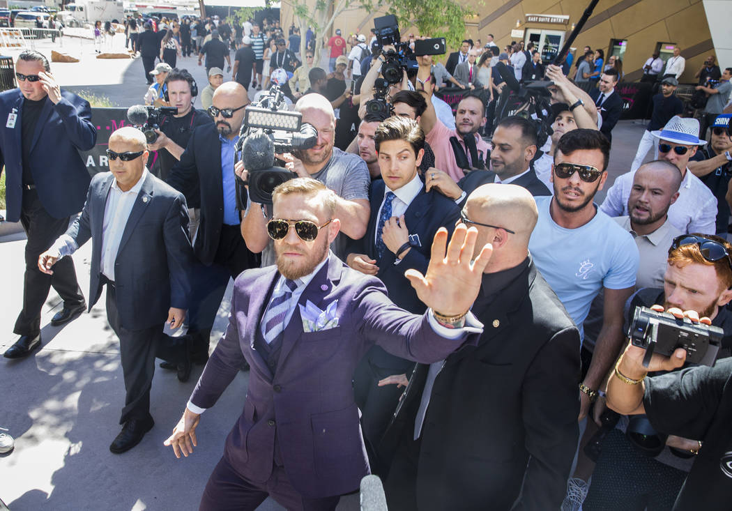 Conor McGregor, middle, waves to fans during his arrival at Toshiba Plaza outside T-Mobile Arena in advance of his Saturday night fight with Floyd Mayweather Jr. Photo taken on Tuesday, Aug 22, 20 ...