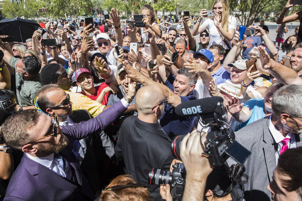 Conor McGregor, left, shakes hands with fans during his arrival at Toshiba Plaza outside T-Mobile Arena in advance of his Saturday night fight with Floyd Mayweather Jr. Photo taken on Tuesday, Aug ...