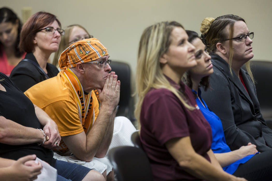 Frank Malley, left, who has children attending Nevada Connections Academy, listens to students speak to the state public charter authority board in hopes to keep the school open during a meeting a ...