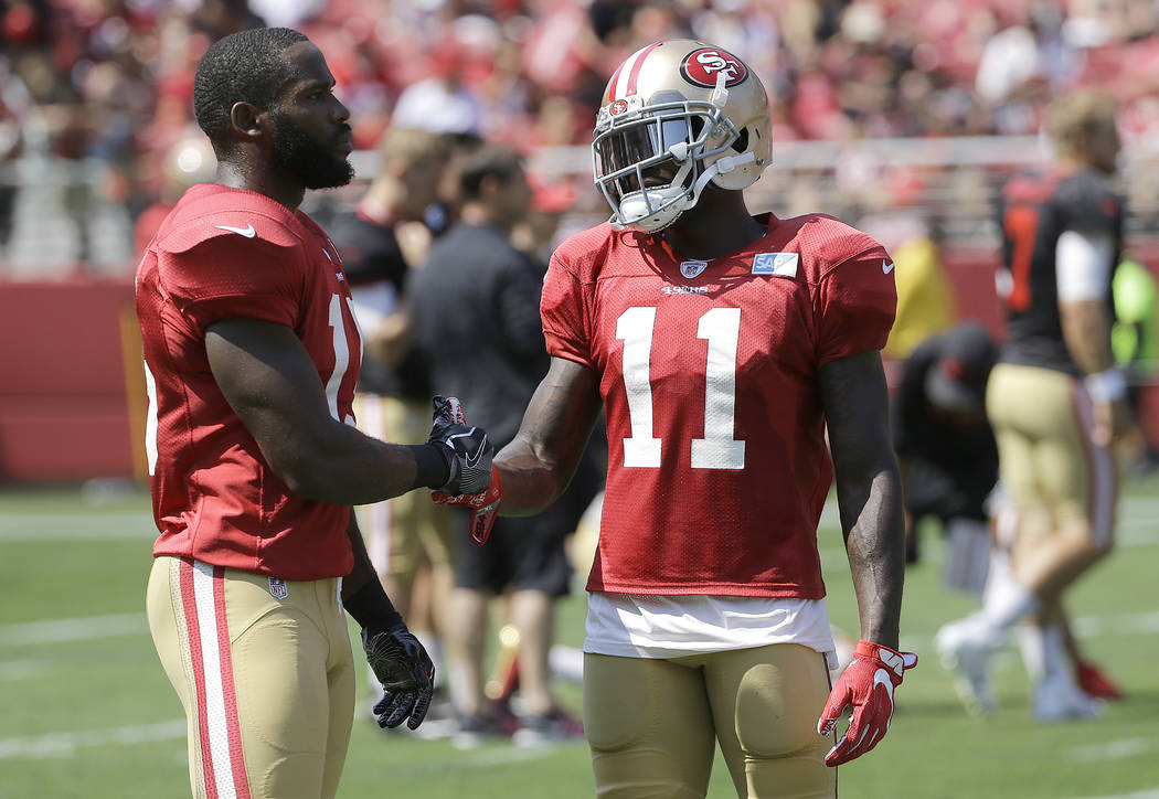 San Francisco 49ers' Pierre Garcon, left, shakes hands with Marquise Goodwin during an NFL football training camp in Santa Clara, Calif., Saturday, Aug. 5, 2017. (AP Photo/Jeff Chiu)