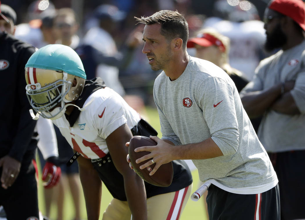 San Francisco 49ers head coach Kyle Shanahan, right, prepares to throw during a joint NFL football practice with the Denver Broncos Wednesday, Aug. 16, 2017, in Santa Clara, Calif. (AP Photo/Marci ...