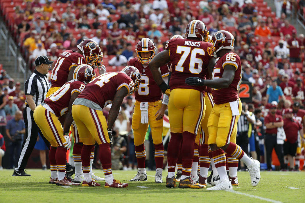 Washington Redskins quarterback Kirk Cousins (8) huddles with teammates in the first half of a preseason NFL football game against the Cincinnati Bengals, Sunday, Aug. 27, 2017, in Landover, Md. ( ...